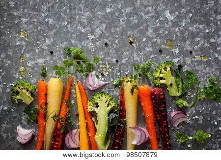 raw rainbow carrot , broccoli and onion for roasting, on the vintage metal background