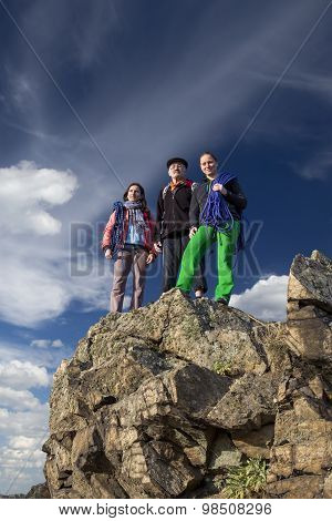 Group of climbers stays on the pointed cliff