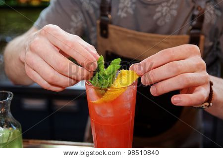 Bartender is adding mint and citrus rind to the cocktail