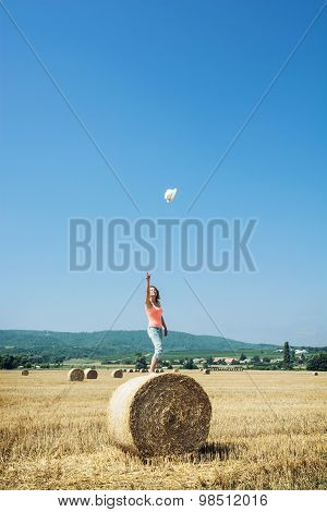 Young Woman Stands On The Haystack And Throws Her Hat High Into The Sky