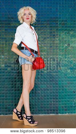 Fashionable beautiful young woman with long legs next to green wall. Indoor