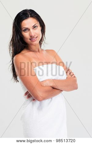 Portrait of a happy woman with towel and wet hair standing with hands folded isolated on a white background