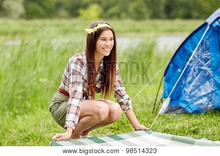 camping, travel, tourism, hike and people concept - happy young woman laying blanket at campsite