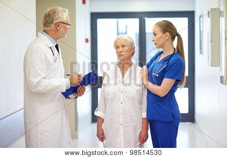 medicine, age, health care and people concept - male doktor with clipboard, young nurse and senior woman patient talking at hospital corridor