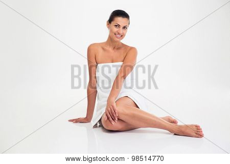 Portrait of a smiling attractive woman in towel sitting on the floor isolated on a white background. Looking at camera