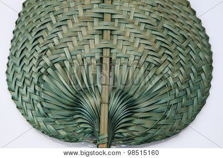 Green color native fan made from palm leaves on white background