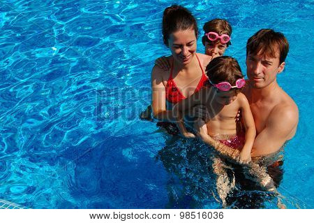 Happy family having fun in swimming pool on summer vacation
