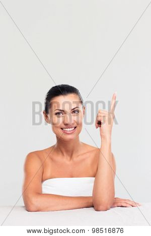Portrait of a happy cute woman in towel sitting at the table and showing finger up isolated on a white background. Looking at camera