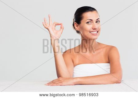 Smiling attractive woman in towel sitting at the table in towel and showing ok sign isolated on a white background