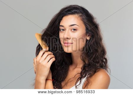 Happy cute woman combing her hair over gray background. Looking at camera