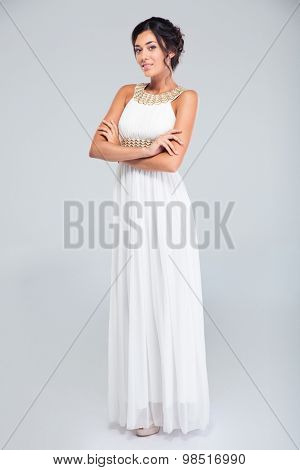 Full length portrait of a lovely woman standing in dress with arms folded over gray background