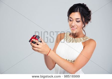 Portrait of a young attractive woman opening jewelry gift box on gray background