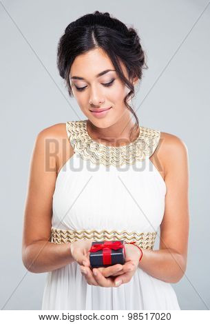 Portrait of a pretty woman holding jewelry gift box on gray background