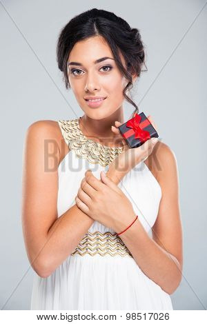 Portrait of a smiling cute woman holding jewelry gift box on gray background