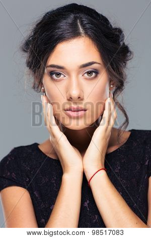 Beauty portrait of a lovely woman looking at camera on gray background