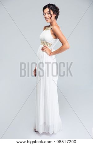 Full length portrait of a smiling woman standing in fashion dress and looking at camera