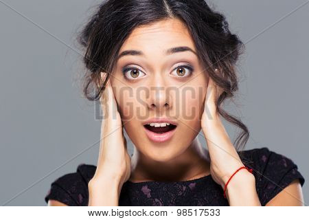 Closeup portrait of surprised woman looking at camera on gray background