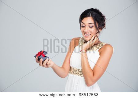 Happy cute woman opening jewelry gift box on gray background