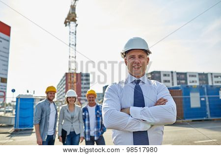 business, building, teamwork and people concept - group of smiling builders and architect in hardhats at construction site