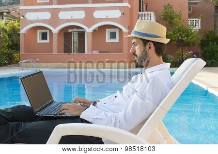 Young Businessman Working On His Laptop By The Pool While On Vacation