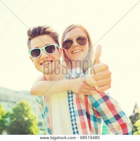 summer holidays, vacation, love, gesture and friendship concept - smiling teen couple in sunglasses having fun and showing thumbs up in park