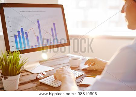 Businessman sitting in front of computer monitor and analyzing data