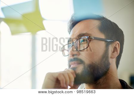 Pensive businessman looking at reminder in office
