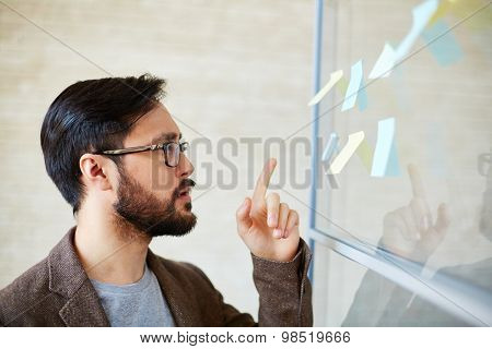 Attractive businessman pointing at notepaper on board