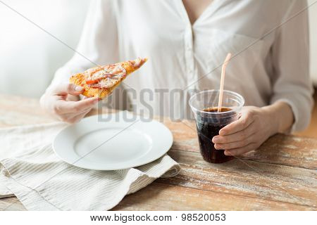 fast food, people and unhealthy eating concept - close up of woman hands with pizza and cola drink sitting at table