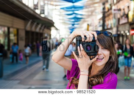 Young woman tourist holding a photo camera