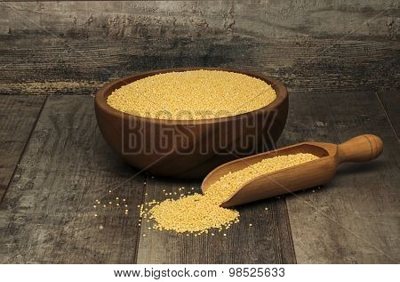 organic millet seeds in a bowl on wooden table