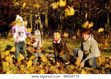 Happy family with two kids throwing leaves in autumn park