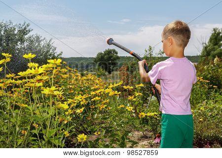 Boy Helps Parents. He Is Watering  Flowers In The Garden.