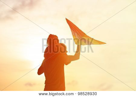 father and little daughter flying kite at sunset