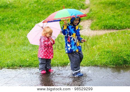 little boy and girl having fun on rain