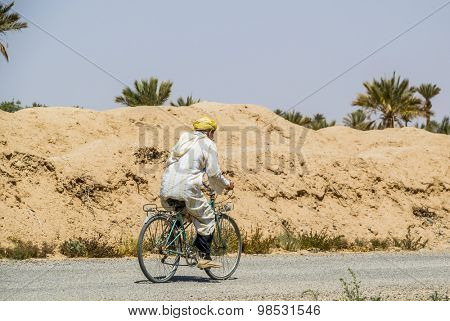 TAFILALT, MOROCCO, APRIL 12, 2015:  Local man in traditional attire rides on bicycle in oasis