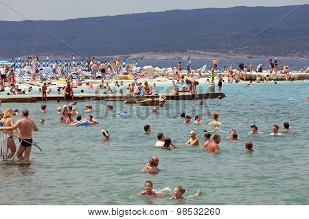 SELCE, CROATIA - JULY 24, 2015: People swimming and sunbathing on the Selce beach
