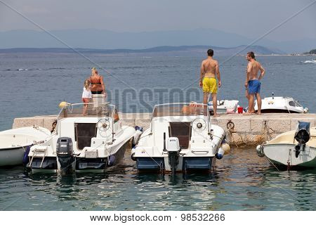 SELCE, CROATIA - JULY 24, 2015: People relaxing and sunbathing on a pier in Marina Selce
