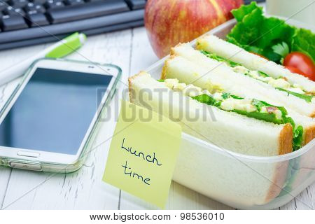 Lunch Box With Egg Salad Sandwiches, Fruits, And Milk On Workplace