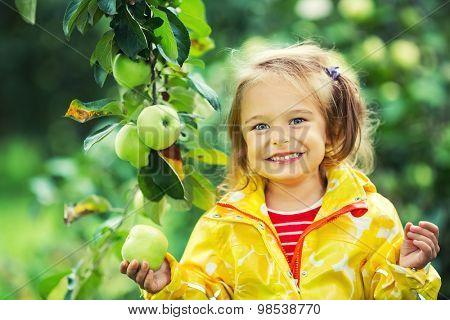 Happy little girl holding apple in the garden