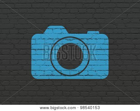 Vacation concept: Photo Camera on wall background