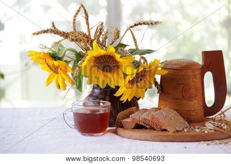 Kvass (kvas) In A Transparent Cup, A Wooden Mug And A Bouquet Of Sunflowers