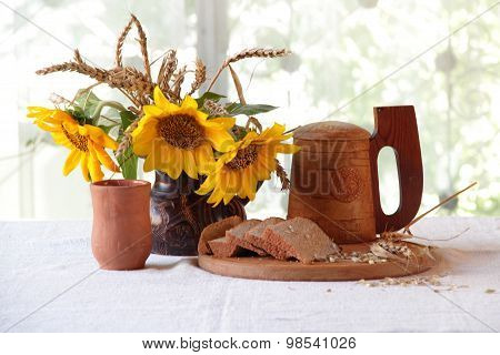Kvass (kvas) In A Transparent Jug, A Wooden Mug And A Bouquet Of Sunflowers