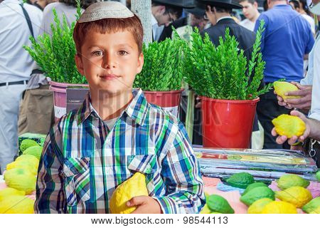 The Jewish holiday of Sukkot. Seven year old boy in white skullcap with etrog. He stand  on a pre-holiday market in Jerusalem. Ritual plants - myrtle prepared for sale