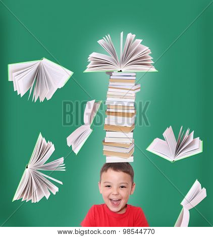 Happy child  with stack of books on his head.