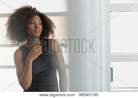 Portrait of a smiling business woman with an afro in bright glass office