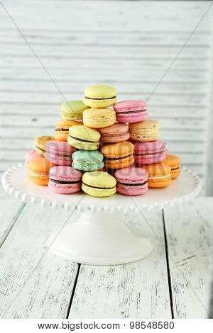 French Colorful Macarons On Cake Stand On White Wooden Background