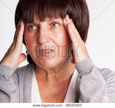 Mature woman has a headache. Sad female