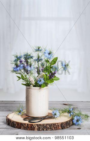 Ceramic pot of wild flowers sitting in the window