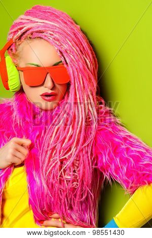 Modern party girl DJ in bright clothes, headphones and with bright dreadlocks. Disco, party. Show business. Bright fashion.